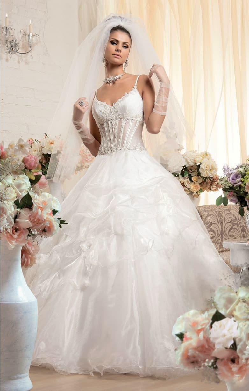 Пышное свадебное платье с изящным декором открытого лифа и полупрозрачным корсетом.