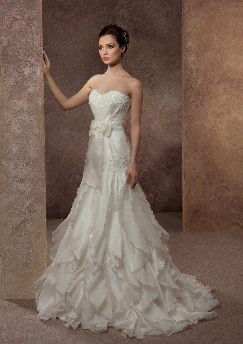 Свадебное платье из глянцевой ткани, спускающейся волнами по элегантному подолу.