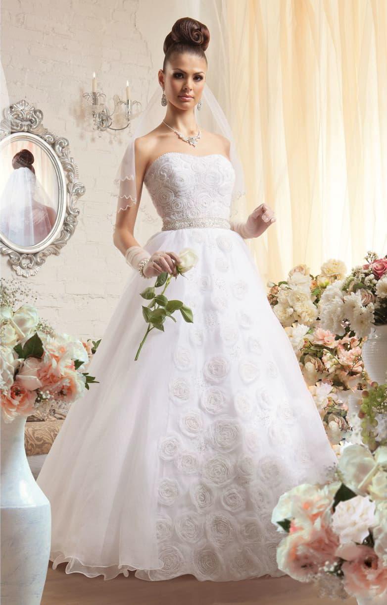 Нежное свадебное платье с деликатным вырезом лифа и бутонами по многослойному подолу.