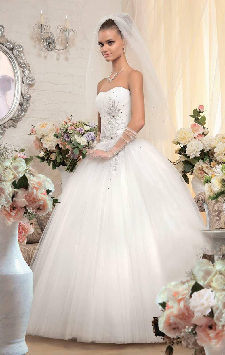 Пышное свадебное платье с серебристой бисерной вышивкой на открытом корсете элегантного кроя.