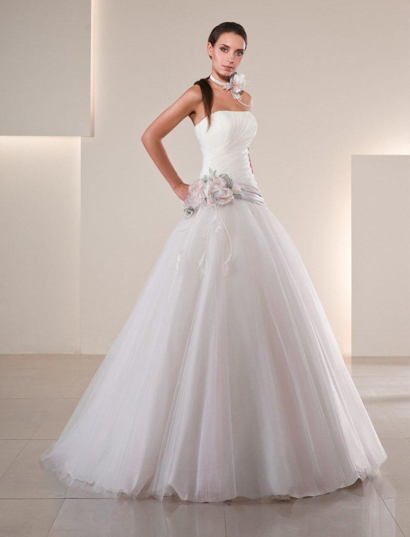 Пышное свадебное платье с лифом прямого кроя и отделкой цветными бутонами на линии талии.