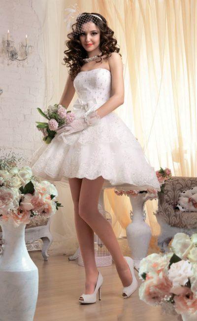 Короткое свадебное платье пышного кроя с бисерной отделкой облегающего корсета.