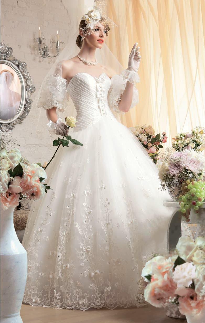 Свадебное платье пышного кроя с открытым корсетом с лифом в форме сердца и объемным декором.