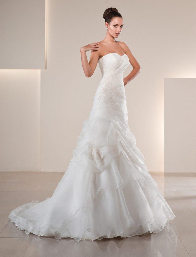 Нежное свадебное платье в классическом стиле, декорированное кружевом и складками ткани.