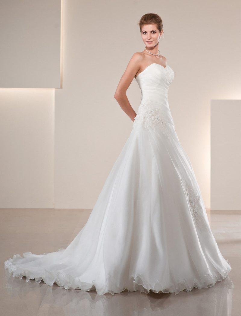 Утонченное свадебное платье с открытым декольте и декором из драпировок и кружева.
