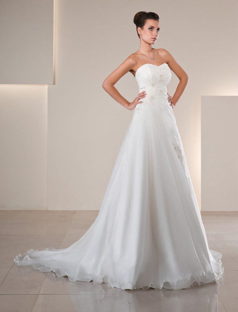 Свадебное платье с традиционным кроем корсета и многослойной юбкой «трапеция» с тонким шлейфом.