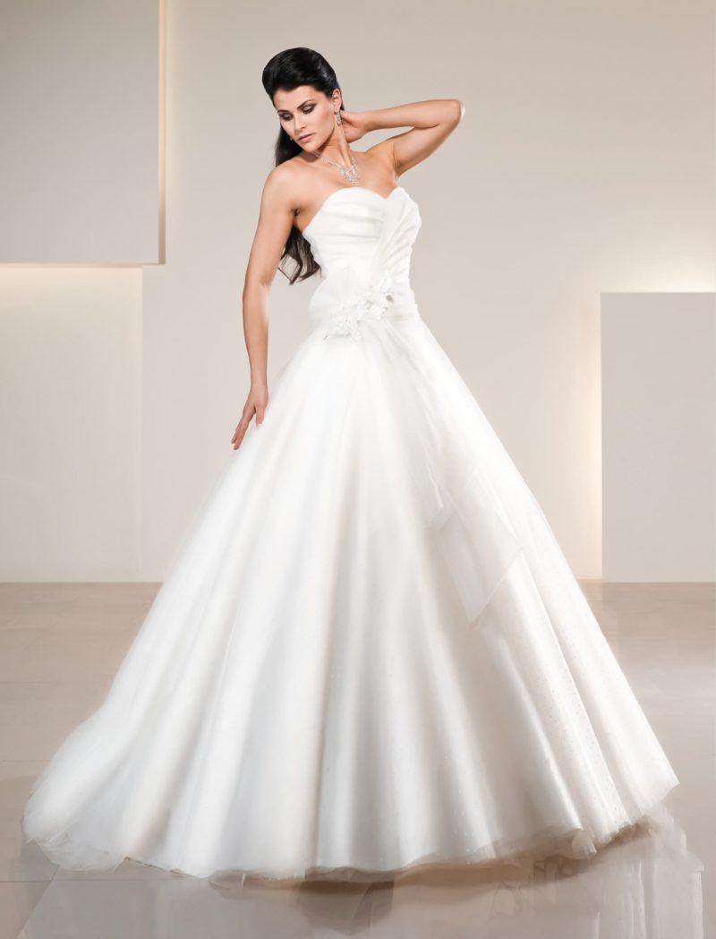 Торжественное свадебное платье с мягким глянцевым блеском, украшенное тонкой тканью.