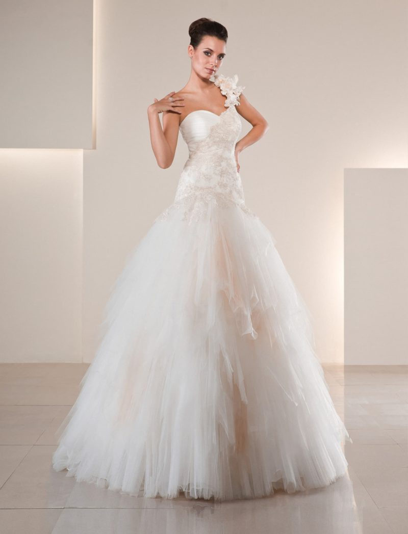 Пышное свадебное платье кремового цвета с асимметричной бретелью и лифом-сердечком.