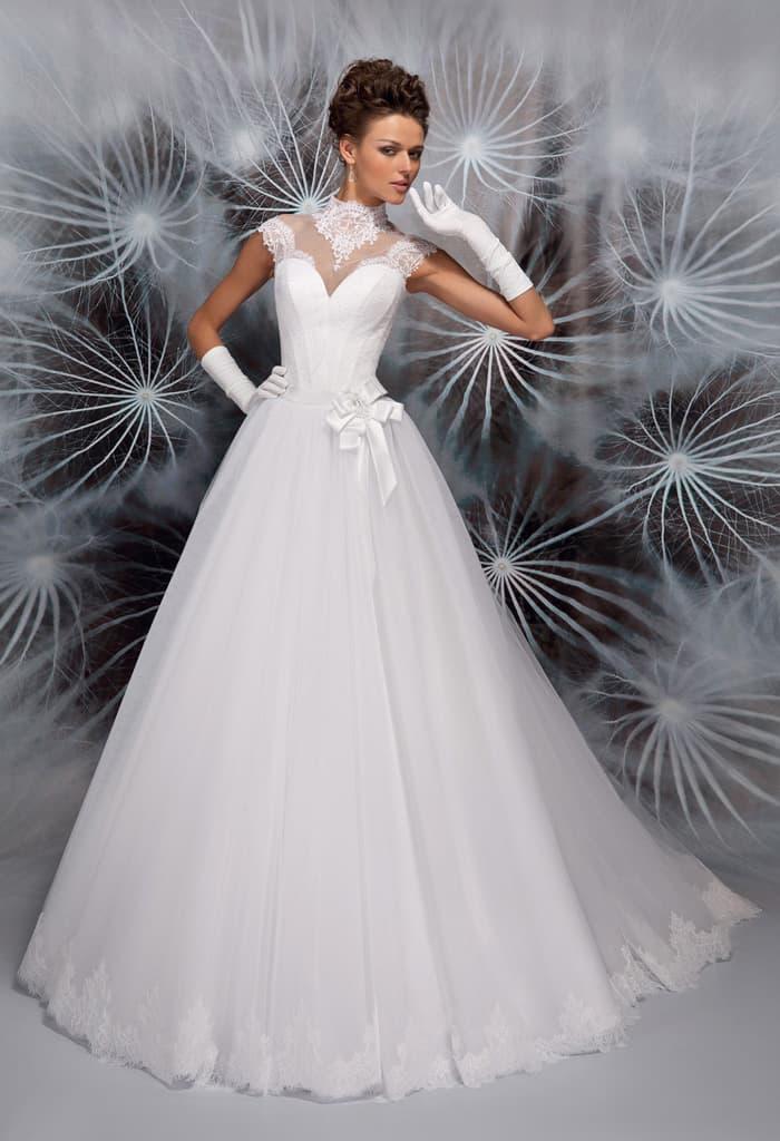 Закрытое свадебное платье пышного кроя с атласным бантом на уровне талии.