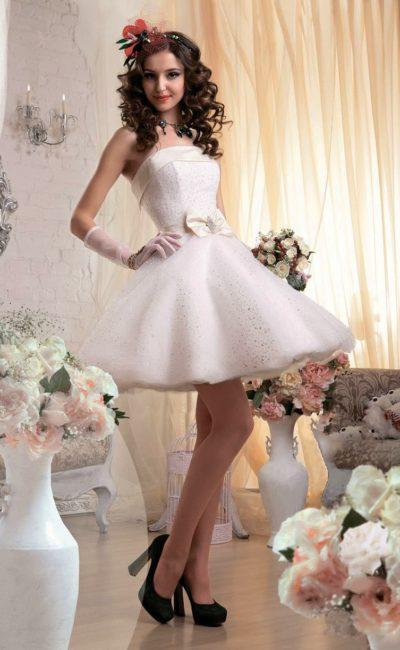 Кокетливое свадебное платье с пышной юбкой до колена и открытым корсетом с атласным декором.