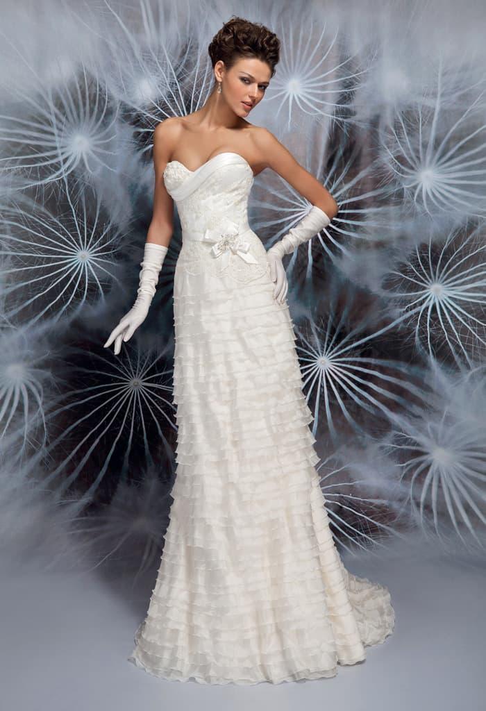 Прямое свадебное платье с открытым декольте и оборками по всей длине юбки.