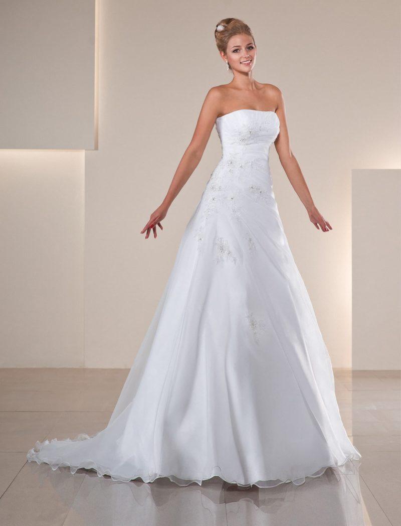 Свадебное платье с романтичным лифом прямого кроя и отделкой полупрозрачной тканью.