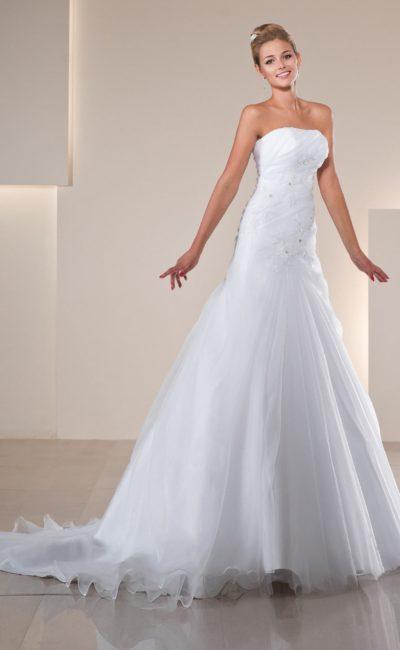 Деликатное свадебное платье с полупрозрачным верхом юбки и облегающим корсетом с вышивкой.