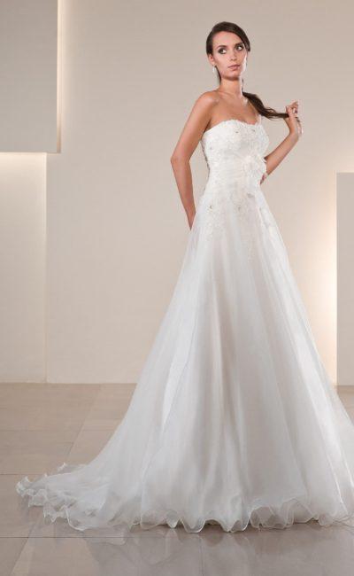 Деликатное свадебное платье с открытым корсетом, украшенным нежной бисерной вышивкой.