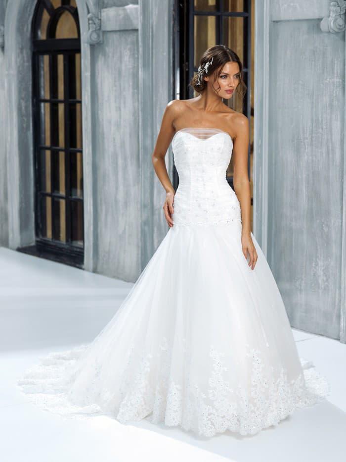 Пышное свадебное платье с нежной полупрозрачной отделкой декольте и многослойным подолом.