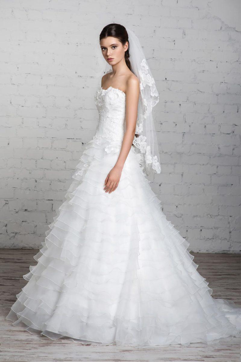 Великолепное свадебное платье с открытым лифом в форме сердца и горизонтальными оборками по подолу.