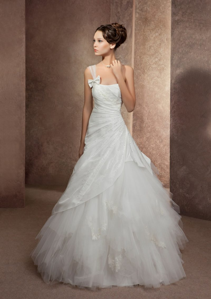 Свадебное платье с драматичной отделкой юбки полупрозрачными оборками и асимметричным лифом.