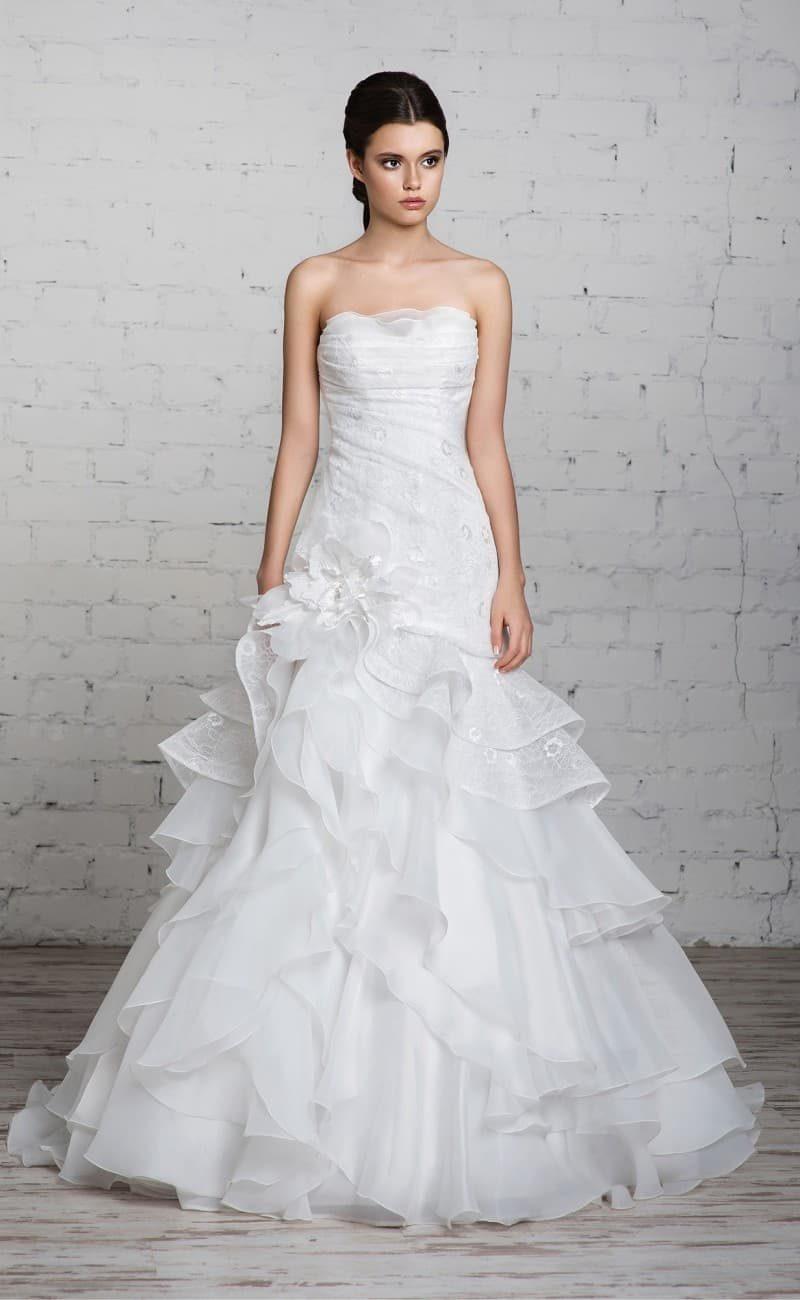 Нежное свадебное платье с крупным бутоном сбоку по подолу и многоярусной юбкой.