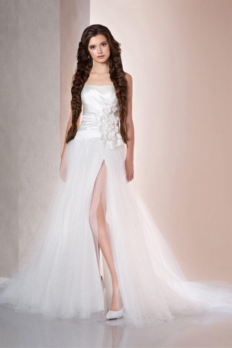 Прямое свадебное платье с открытым лифом, воздушным декором подола и разрезом на юбке сбоку.