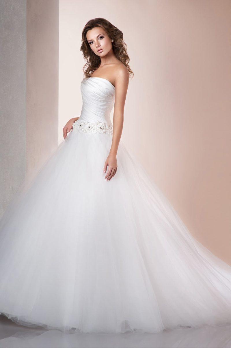 Воздушное свадебное платье с многослойным низом подола и открытым корсетом с драпировками.