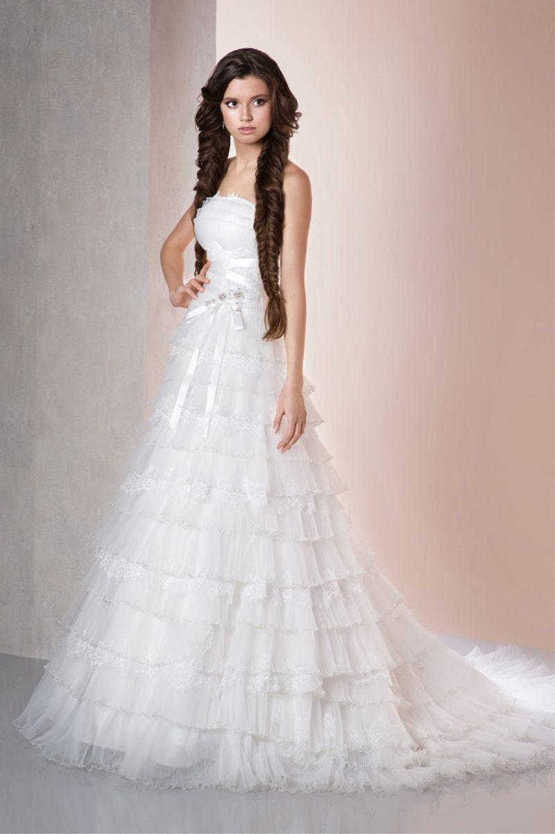 Открытое свадебное платье силуэта «принцесса» с множеством оборок по юбке.