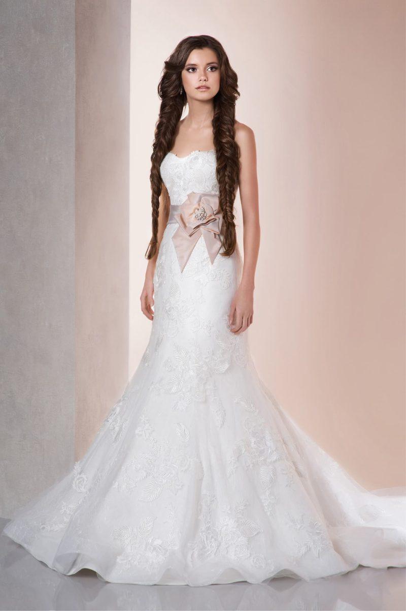 Кружевное свадебное платье «русалка» с широким розовым поясом из атласной ткани.