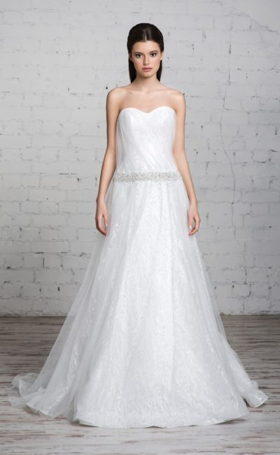 Изысканное свадебное платье с открытым лифом, тонкой верхней юбкой и сияющим поясом на талии.