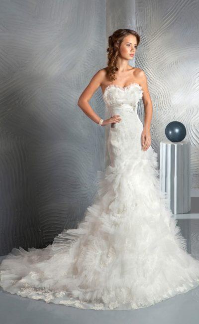Роскошное свадебное платье с открытым лифом и полупрозрачной объемной отделкой по подолу.
