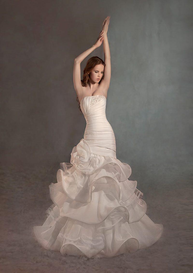 Свадебное платье цвета слоновой кости с силуэтом «рыбка», подчеркнутым оборками на юбке.