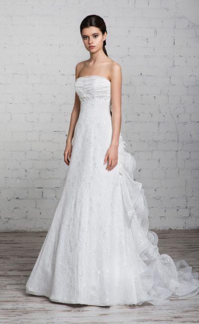 Свадебное платье прямого кроя с открытым лифом и полупрозрачными оборками, создающими шлейф.