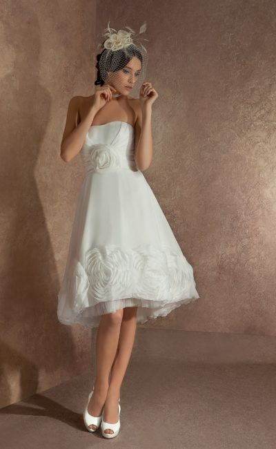 Короткое свадебное платье с открытым лифом и эксцентричной объемной отделкой низа подола.