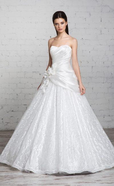 Сияющее свадебное платье с открытым лифом и отделкой драпировками и глянцевым кружевом.