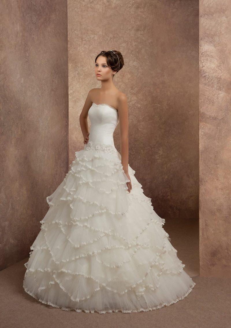 Открытое свадебное платье пышного кроя с причудливыми волнами тонкой ткани по подолу.