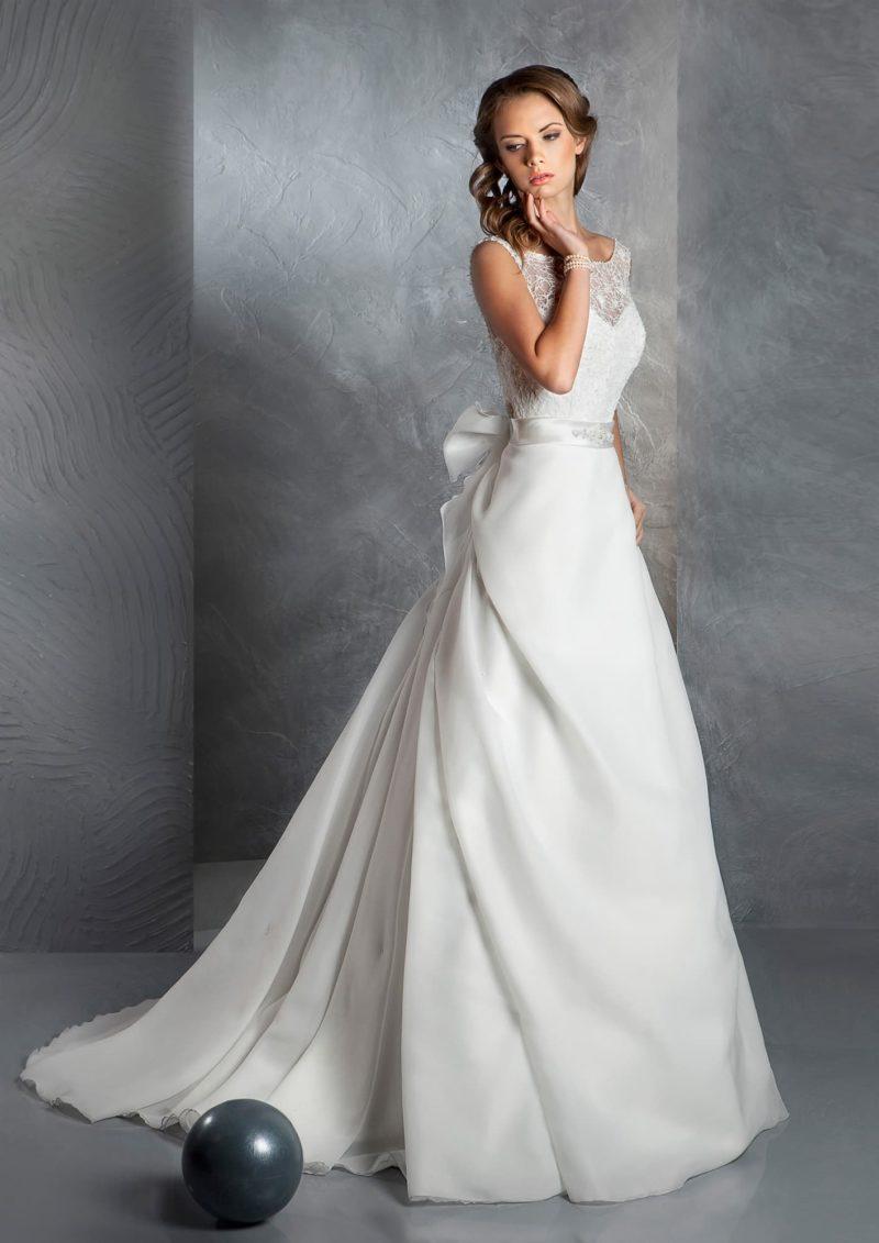 Закрытое свадебное платье «принцесса» с глубоким вырезом на спинке и пышным бантом на талии.