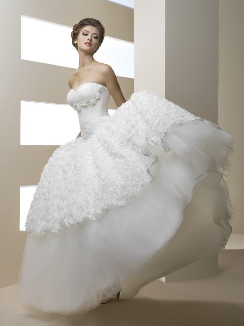 Роскошное свадебное платье с кружевным верхом подола и бутонами под открытым лифом.