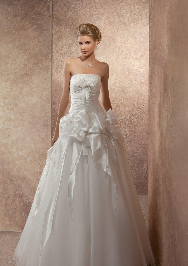 Великолепное свадебное платье с открытым корсетом из атласа, украшенным бантами и лентами.
