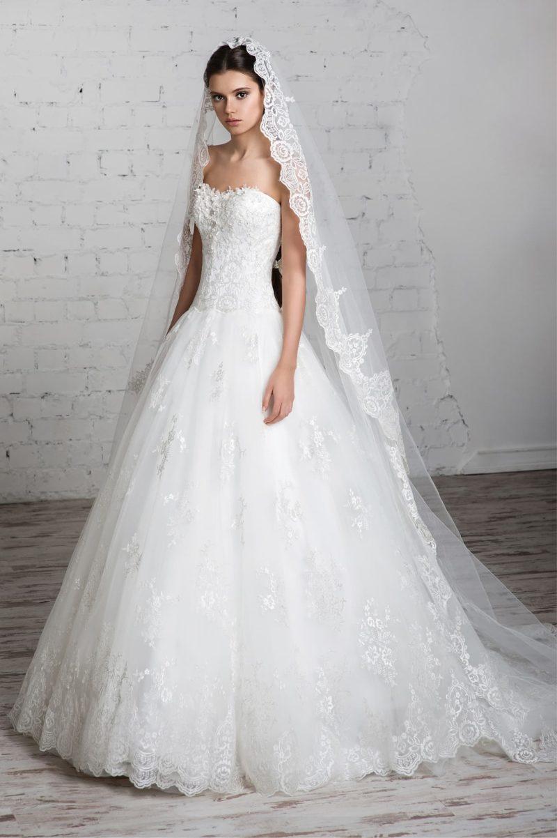 Пышное свадебное платье с кружевной отделкой юбки и открытым корсетом с фактурным декором.