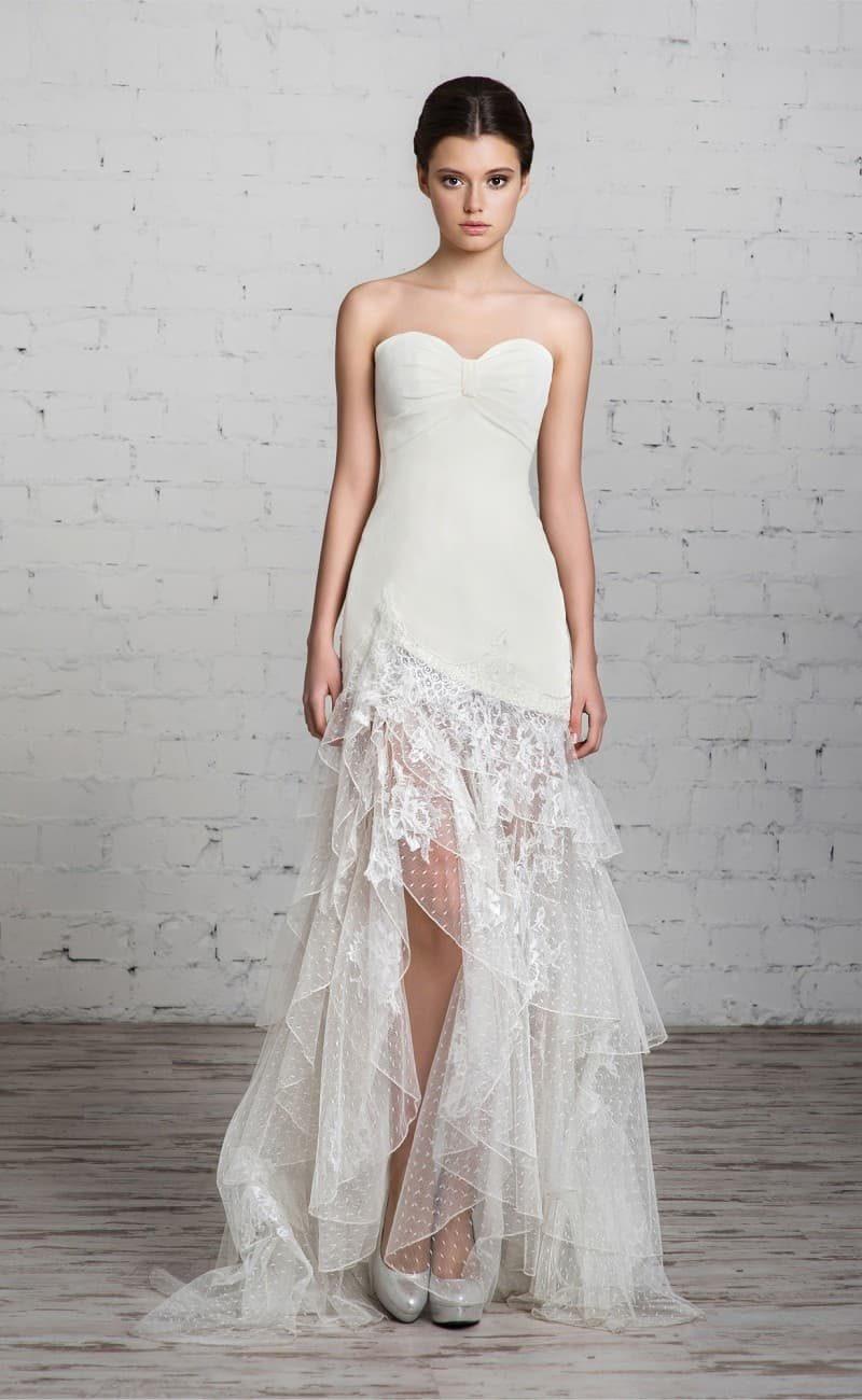 Необычное свадебное платье с изящным верхом и полупрозрачной юбкой с оборками и разрезом.