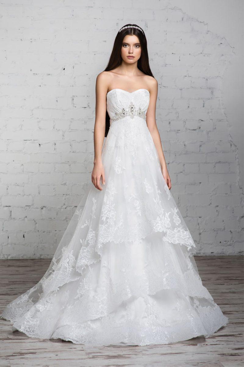 Свадебное платье с многоярусной юбкой, украшенной кружевом, и открытым лифом в форме сердца.