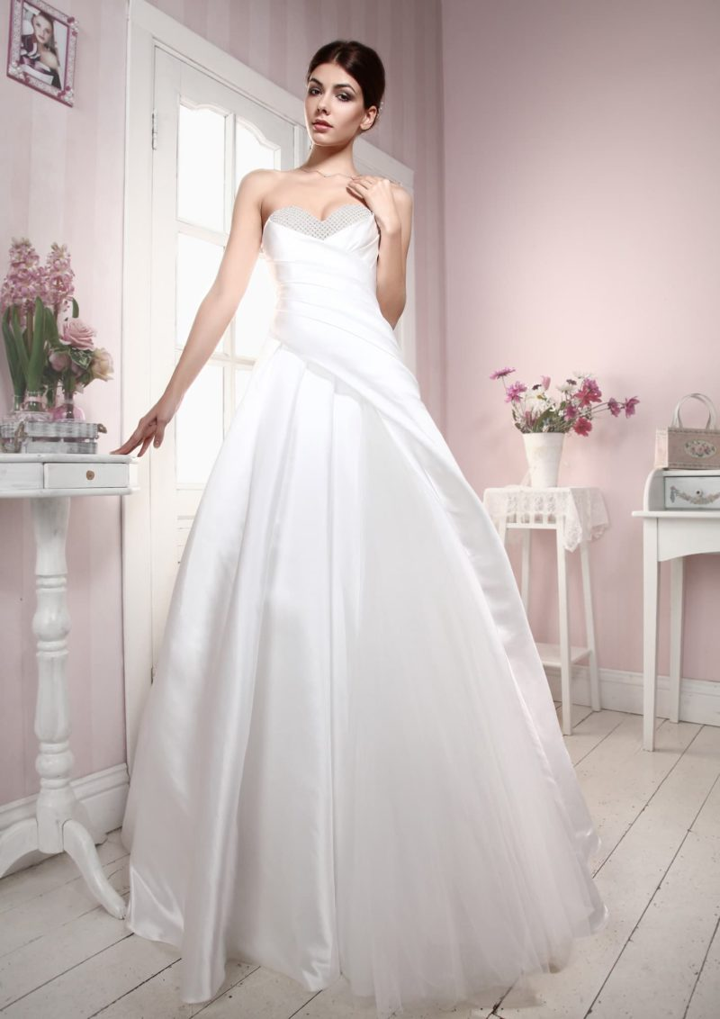 Атласное свадебное платье пышного кроя с открытым лифом, украшенным по краю бисером.