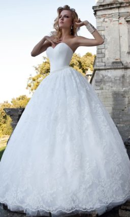 Утонченное свадебное платье с открытым декольте и объемным декором многослойного подола.