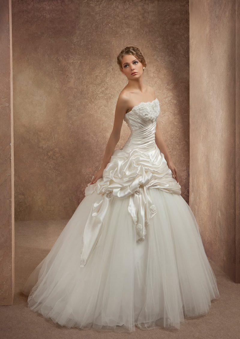 Пышное свадебное платье с лаконичным открытым декольте и атласной отделкой верха подола.
