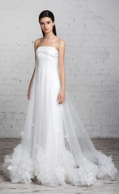 Драматичное свадебное платье с открытым лифом прямого кроя и прозрачной верхней юбкой.