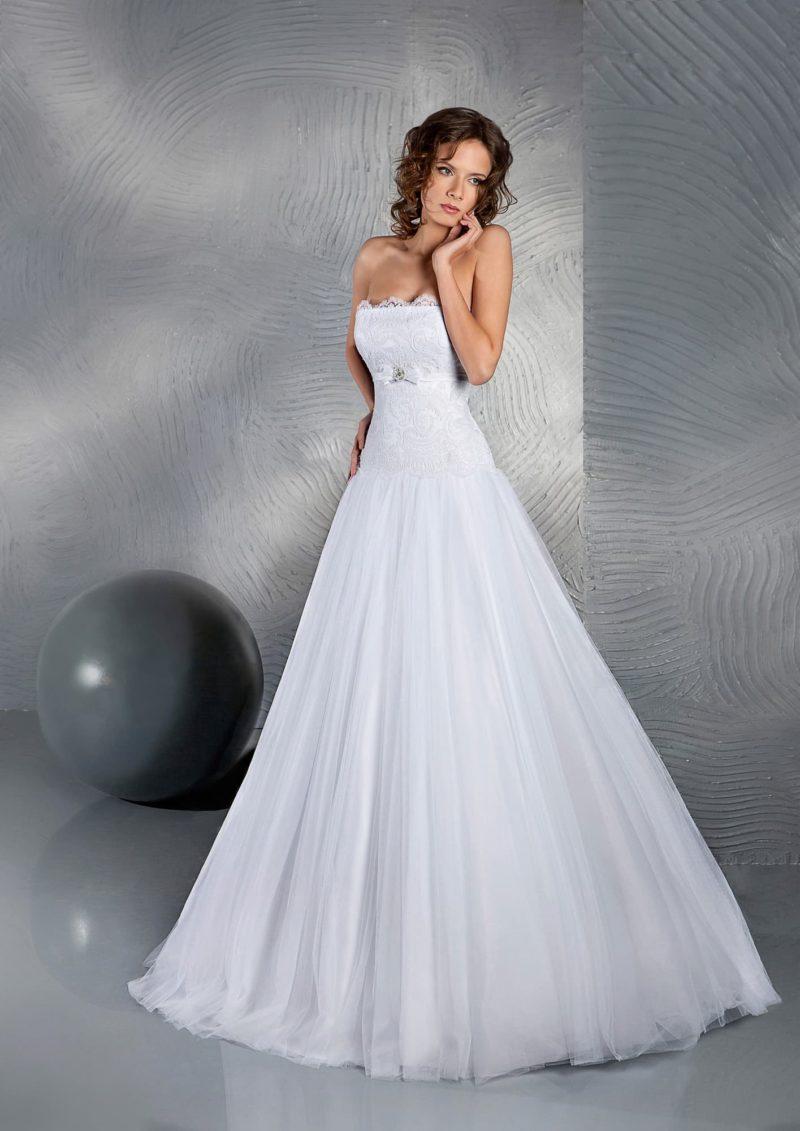 Лаконичное свадебное платье «трапеция» с открытым лифом прямого кроя, украшенным кружевом.