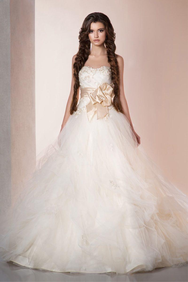 Пышное свадебное платье с фактурным верхом и кремовым поясом из атласа.