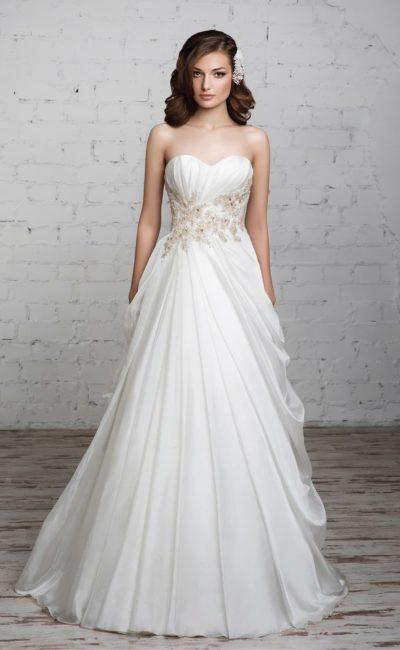 Свадебное платье с открытым декольте, романтичным декором и оборками по многослойной юбке.