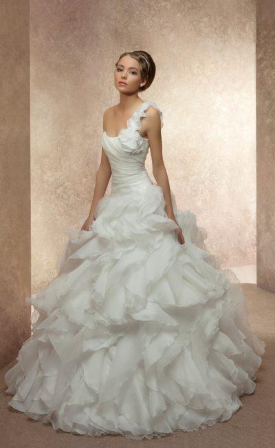 Очаровательное свадебное платье с объемной бретелью над открытым лифом и пышной юбкой.