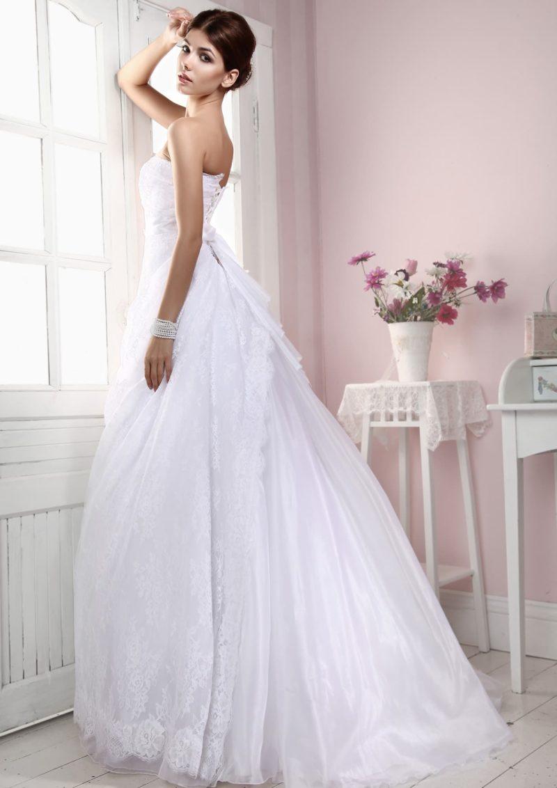 Лаконичное свадебное платье с деликатной юбкой, покрытой кружевной тканью, и открытым декольте.