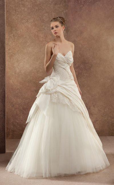 Фактурное свадебное платье пышного кроя с изысканным открытым декольте и многослойным подолом.