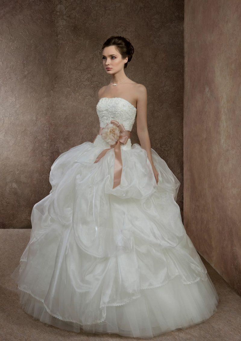 Открытое свадебное платье с роскошными оборками по юбке и цветным поясом с бутоном сбоку.